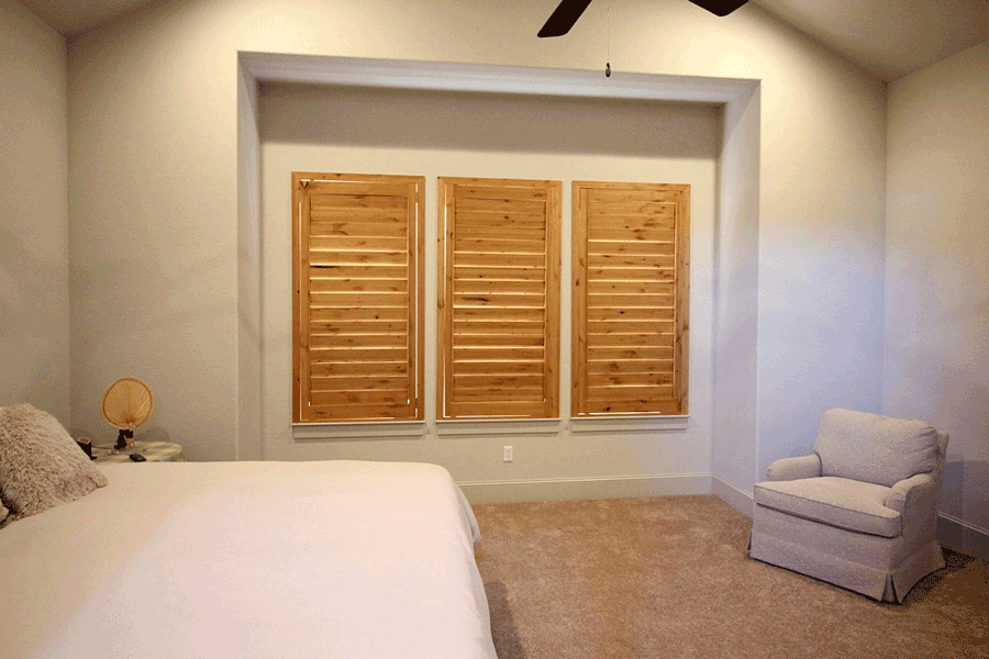Closed plantation shutters on a set of three windows in a San Antonio home.
