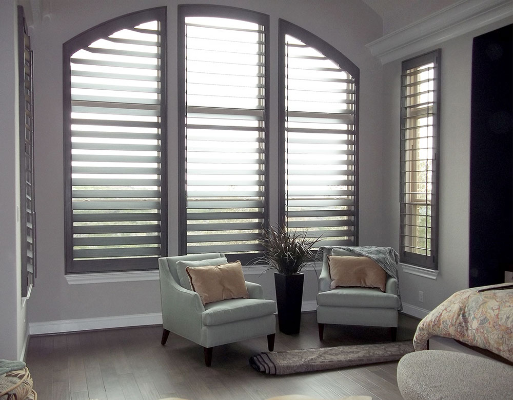 large arched window in San Antonio TX living room with real wood shutters