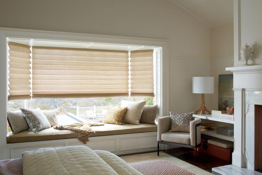 bay window seat area in bedroom with gold fabric roman shades in San Antonio TX