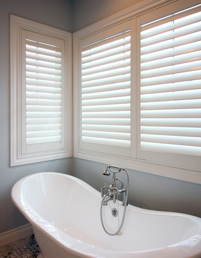 bathroom with stand alone bath tub and interior shutters in San Antonio