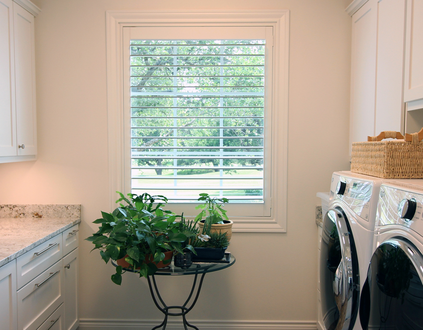 laundry room with green plants woven basket and white plantation shutters San Antonio