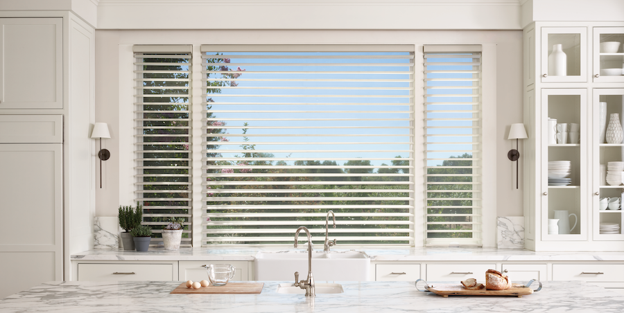 Kitchen sink with window above features nature-inspired sheer Hunter Douglas shades