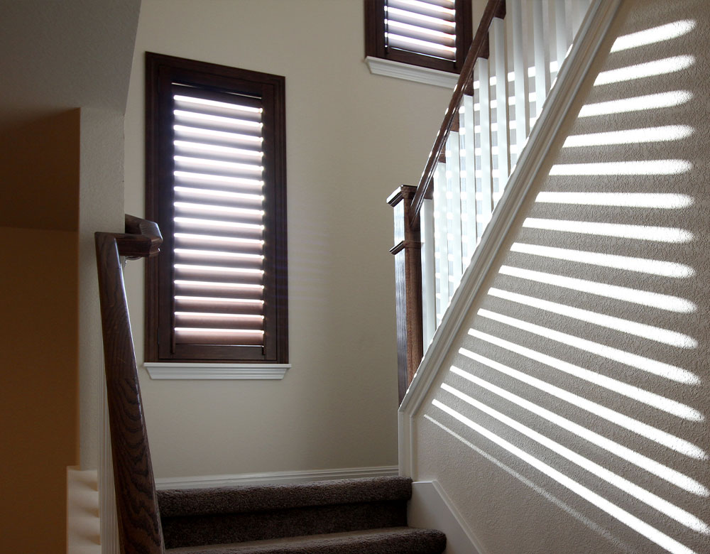 staircase with dark wooden stained window shutters in San Antonio TX home