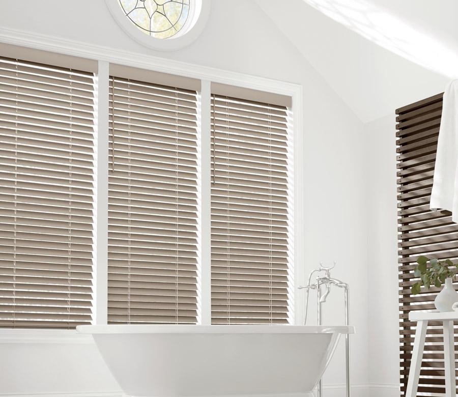 three windows in San Antonio bathroom with neutral faux wood blinds