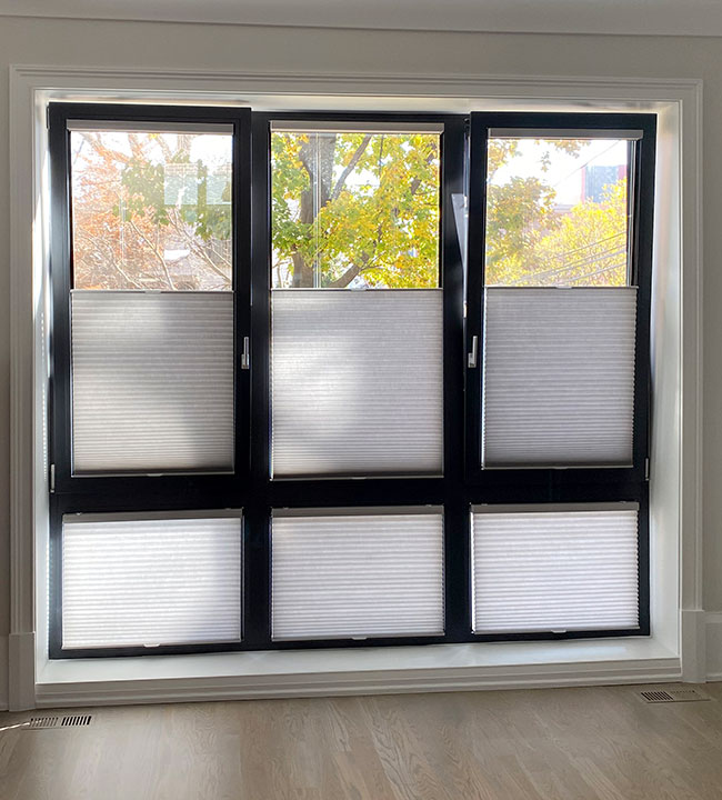 black framed european style windows covered with cellular shades in San Antonio TX