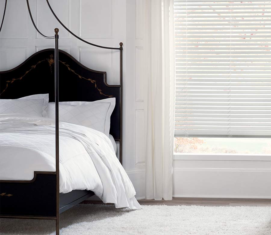 white wooden shades in white bedroom